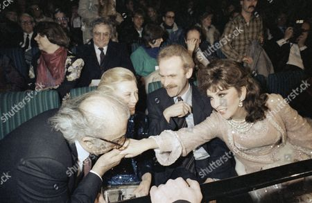 Italian director Federico Fellini greets Italian filmstar Gina Lollobrigida with a kiss on the hand at the opening ceremony of the 36th International Berlin Film Festival on . Gina Lollobrigida is the president of the international jury. Next to Fellini is his wife Giulietta Masina and West Berlin's Senator of Cultural Affairs Volker Hassemer