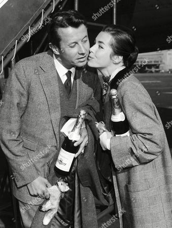 """French actor Michel Auclair is greeted by German actress Marianne Koch upon his arrival on at the Tempelhof airport in Berlin, Germany. They will both star in the film """"Der Fuchs von Paris"""" (The Fox of Paris) directed by Paul May"""