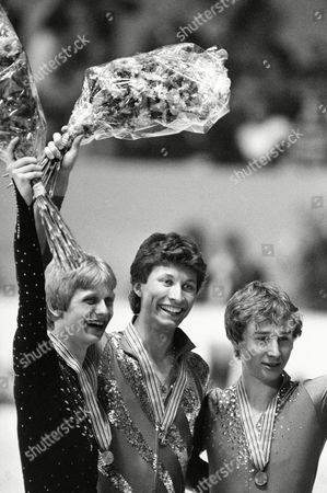 Gold medal winner Norbert Schramm, center, from West Germany shares a smile with 2nd placer Jozef Sabovcik from Czechoslovakia, left, and 3rd placer Alexandre Fadeev, right, from Soviet Union during men's winning ceremony at the European Figure Skating Championships in Dortmund, West Germany on