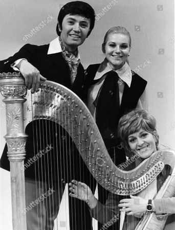 "Stock Photo of Rex Gildo; Peggy March; Siw Malmkvist Posing with a harp from left to right are German crooner Rex Gildo, singers Peggy March and Siw Malmkvist on in a studio of the Hesse Broadcast Company in Frankfurt, Germany prior to the preliminary decisions for the European song competition ""Grand Prix Eurovision de la Chanson"