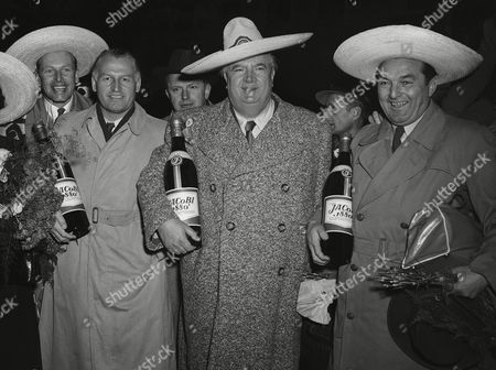 "Wearing sombreros and holding big rum bottles, from left to right: co-driver Hans Klenk, race driver Karl Kling, Alfred Neubauer, coach of the Mercedes racing team and race driver Hermann Lang, at their arrival on at the airport in Stuttgart, Germany after their win of the ""Carrera Panamericana"" race"