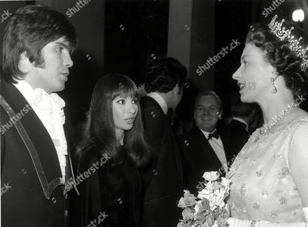 Her majesty Queen Elizabeth II, talks to Israeli singer and composer Abi Ofarim (Abraham Raichstadt), left, and wife Esther Ofarim (Esther Zaid), at the Palladium in London, England, after attending a special performance in aid of the British Olympic Appeal Fund