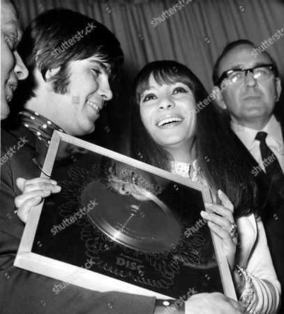 "Israeli singer and composer Abi Ofarim (Abraham Raichstadt), left, and wife Esther Ofarim (Esther Zaid), whose recording ""Cinderella Rockafella"" is currently at No. 1 in the British Hit Parade, are pictured with the silver disc presented to them at the reception in London, England, after sales of the record topped 250,000"