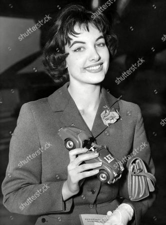 """Petra Schuermann Petra Schuermann, 23-year-old student who won the """"Miss World"""" contest in London, United Kingdom, leaves London airport en route home to Germany on October 17, 1956. She caries a model of the car presented to her by a London garage organisation after her victory"""