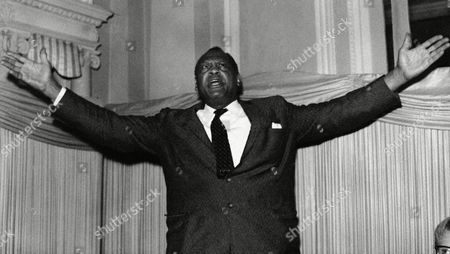 Paul Robeson, the 60-year-old Negro singer, renders a song during a press conference he gave at the Empress Club in London, United Kingdom,, following his arrival from the United States. He was given a hero's welcome in Britain in afternoon on his first visit out of the United States after eight years without an American passport. Robeson, who plans a series of concerts in Europe, had been restricted from traveling aboard since 1950. Supporter of communist-front causes and a winner of the Stalin Peace Prize, he was denied a passport because he repeatedly refused to sign a non-communist affidavit which the state department required before issuing a passport. A Supreme Court decision outlawed the requirement