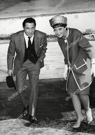 """British actor Richard Todd and actress June Thorburn duck beneath the wing of a plane at London Airport, United Kingdom,, as they left for Nice to attend the current International Film festival at Cannes, France. They are presenting the official British entry in the festival """"Don't Bother to Knock"""