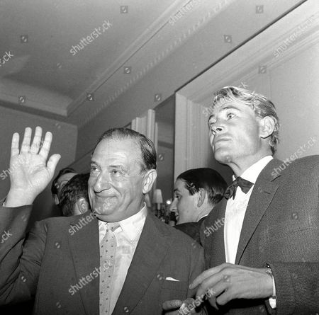 """Austrian-born American film producer Sam Spiegel waves as he poses with Irish actor Peter O'Toole during a reception at Claridges, London, United Kingdom on to the cast of """"Lawrence of Arabia"""" to mark their return from Jordan where the picture was shot on location. O'Toole has the title role as the legendary Lawrence who led the Arabs against the Turks in World War I"""