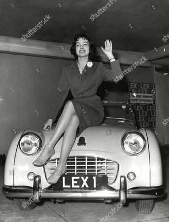 """A GIFT FOR """"MISS WORLD"""": Petra Schuermann, 23 years old """" Miss Germany """" who won the """"Miss World"""" contest in London last night was today, presented with a Triumph T.R. 3 car by the directors of Lex Garages limited, Lexington Street, Piccadilly. A number of the other contestants turned up to take part in the presentation ceremonies. Photo shows: """"Miss World"""" waves from the bonnet of her new car"""