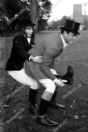 Decked out in hunting costume, actress Fenella Fielding gets her leg pulled by American actor Tony Curtis, as they clown around between takes at Shepperton Studios, Middlesex, England, United Kingdom,, where they are working on a film