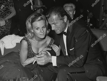 "West German singer and actress Heidi Bruehl, tenderly holds the arm of U.S. American actor Lex Barker, during the opening of 13th International Film Festival ""Berlinale"" by Lord Mayor Willy Brandt, in West Berlin, West Germany"