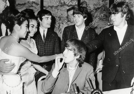 More or less on their way to Australia, the Beatles are introduced to Thai film stars Busara Narumit, extreme left, and Unchuli Anantakul while attending the second semifinal of the Miss Hong Kong Beauty Pageant in Hong Kong, on . Looking fey with a cigarette is George Harrison; behind him are Jimmy Nicol, Ringo's stand-in, left, Paul McCartney and John Lennon. The group was met at the airport in the day by 3,000 screaming fans. The lads leave for Australia and reunion with Ringo on Wednesday