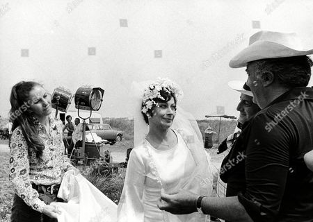 """Federico Fellini, the Italian film director, at right gives instructions to French actress Magali Noel (wearing wedding gown) on set of the movie """"Amarcord"""" near Bologna, Italy in 1973. The movie was awarded the Oscar prize as best film in foreign language on in Santa Monica, California. Others unidentified"""