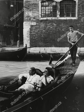 U.S. American actress Rita Hayworth, and American actor Gary Merrill (former husband of Bette Davis) take a sightseeing tour in a traditional gondola on a canal in Venice, Italy, . The two artists met here where they are presently vacationing