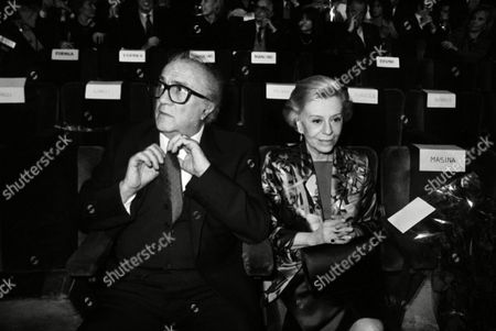 """Italian movie director Federico Fellini adjusts his tie, sitting next to his wife Giulietta Masina during the premiere of his latest movie """"Ginger e Fred"""" on Tuesday night, in Rome, Italy. An audience of 2,000 top personalities gave the film a ten minute standing ovation when the lights came on"""