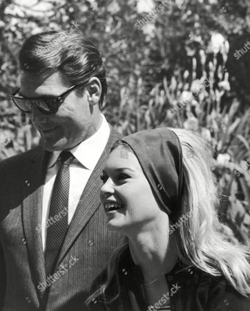 "American actor Jack Palance and French actress Brigitte Bardot walk through the gardens of a villa at the outskirts of Rome, Italy, on during a break of the film ""A ghost at Noon"" in which both are starring. The villa, on the ancient Appian Way, was taken over by the production for exterior scenes. ""A ghost at Noon"", from the novel of Italian author Alberto Moravia called ""IL Disprezzo"" (The Contempt), is directed by France's Jean-Luc Godard"