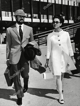 """Hollywood actor Tony Curtis and his German-born wife, actress Christine Kaufmann walk at Rome's Fiumicino airport in Italy,, toward a plane that will take them to New York. Curtis has just completed the shooting of a new film, """"On my way to the Crusades I met a girl who..."""", directed by Italian Pasquale Festa Campanile and with Italian actress Monica Vitti in the leading female role"""