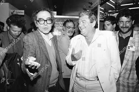 """Swiss movie director Jean-Luc Godard and Israeli producer Menahem Golan gesture as they discuss in front of newsmen in Cannes, France, after the screening of Godard's out of competition """"King Lear"""", produced by Cannon group, as part of the 40th Cannes Film Festival"""