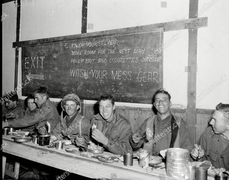 "Balog Dulac Tonderella Members of a rifle team of the Second Battalion, Fifth Marine Regiment, dig in at Thanksgiving dinner in a mess hall in Chosin Reservois, North Korea, . From left are: Cpl. James Balog, Pfc. Richard Dulac, and Nunzio Tonderella. On the blackboard ""pogey bait"" refers to treats such as candy and junk food"