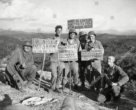 Stock Photo of A group of American GIs, part of the force which had just recaptured an allied patrol base on the western front in Korea, display signs left by the fleeing Chinese, who gave up the position to 1st cavalry division troopers. Left to right are : Lieut. Albert E.Dru, Zelienople, pa; Pfc. William j. Dunsdale, West Warwick, R.I.; l/c Dan W. rivers, Franklin, Tenn.; Corp. Vernon P. Langford, Brookston, Ind.; Pfc. Paul M. George, Gilmore City, Ia.; and Lieut. Dick Walther, Pittsburgh, Pa