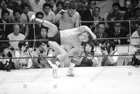 Leon Spinks, Koji Sasahara Leon Spinks, background, a former heavyweight boxing champion of the world evades a flying kick by Japanese professional wrestling champion Antonio Inoki in the 6th round of their scheduled 12-round boxing vs wrestling match in Tokyo, . Inoki pinned Spinks to the mat for five seconds