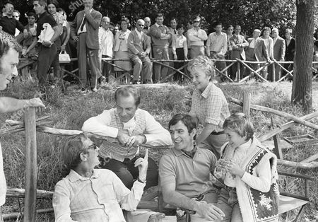 "British director-producer-writer Lewis Gilbert, Italian actor Rossano Brazzi, Yugoslav actor Bekim Feyum, Hollywood actress Olivia De Havilland, and an Italian boy, Loris Loddi are chatting together on during a break in rehearsal work in Rome's public park ""Villa Borghese"" for a new film, ""The Adventurers.&quot"