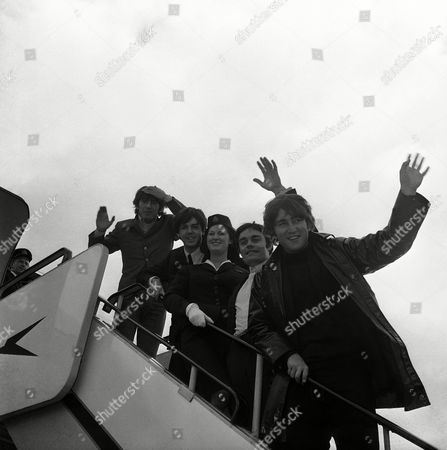 Windswept and waving, the Beatles arrive at London Airport in England from Amsterdam,, after a three-day trip to the Netherlands. From left: George Harrison, Paul McCartney, Stewardess Anne Creech of Liverpool, drummer Jimmy Nicol, and John Lennon. Nicol is deputizing for Ringo Starr who is ill
