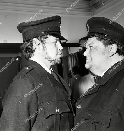 Former British and World Middleweight Boxing Champion, Terry Downes, left, and British actor Denis Shaw in the uniforms of prison warders, in London,, when they went for costume fitting for the new stage play, Inside Out, which opens in London at the Royal Court Theatre