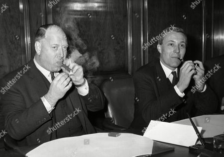 Postmaster General Anthony Wedgewood Benn, right, lights his pipe while Dr. Richard Beeching, Chairman of the British Railways Board, puffs on his cigar during a press conference at Post Office Headquarters, in London, on . After meeting newsmen they signed an important contract for the conveyance of parcel mails by rail, aimed specifically ar improving service to the public
