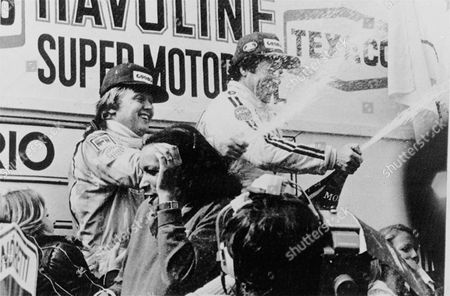 Ronnie Peterson, left, second and the USA's Mario Andretti, who won the Grand Prix of Belgium, both driving a Lotus, pouring champagne over the crowd during podium ceremony after the Grand Prix