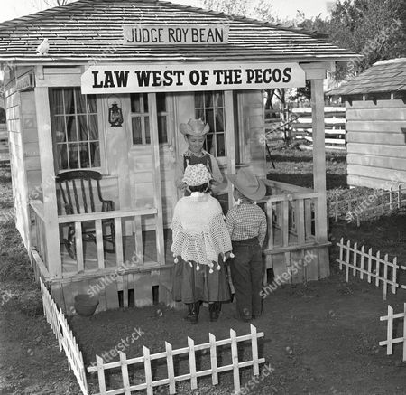 What would a frontier town be without a Justice of the Peace and Learado has one. Going through a mock wedding at the Justice's house are Pam, 4-year-old daughter of the Robert Sutherlands, and Chris, 6, a nephew of the Sutherlands. On porch acting the part of Judge Roy Bean is Tommy Sutherland, 6, another nephew on