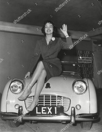 """Miss Germany A gift car for 'Miss World"""". Petra Schuermann, 23-Yeahr-Old """"Miss Germany"""" who won the """"Miss World Contest in London last night, was today presented with a Triumph T.R.3. Car by the directors of Lex Garages Limited, Lexington Street, Picadilly. A number of the other contestants turned up to take part in the presentation ceremonies. The AP-Photo shows. """"Miss World"""" waves from the Bonnet of her New car"""
