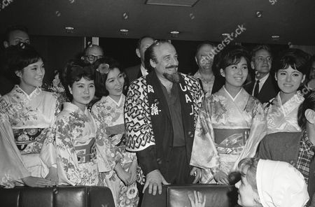Surrounded by a bevy of kimono-clad Japanese beauties, American maestro Mitch Miller enjoys a tumultuous welcome at Tokyo's International Airport, during his recent arrival there. On his first overseas tour, Miller will be appearing in Japan with his male chorus, a group of girl dancers and some key musicians from the U.S backed by the Tokyo Union orchestra