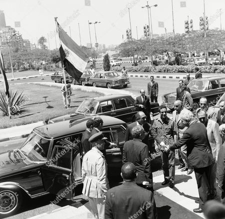 Stock Image of Muammar Muhammad al-Gaddafi Egyptian President Anwar Sadat shaking hands with an unidentified ASU member while Muammar Gaddafi looks at them upon arrival at the Arab Socialist Union building in Cairo, Egypt in July 1973 during their meeting with secretaries of the ASU districts