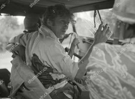 Bleeding from a back wound, Australian journalist Neil Davis talks with a Cambodian army officer on Route 4, near Mohasaing, . Davis, a veteran of Indochina war coverage, was caught in a mortar barrage 36 miles from Phnom Penh. His wound was not considered serious