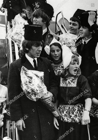 Ready for laughs as ever, the Beatles put on astrakhan hats as they are greeted by girls in national costume on their arrival at Amsterdam Airport for a three-day visit to the Netherlands, on . Top left is John Lennon, Jimmy Nicol, stand-in drummer for Ringo Starr, Paul McCartney, right, and George Harrison at the front
