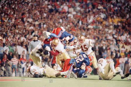 The Univ. of Florida's Emmitt Smith(22) is stopped by the Florida State defensive wall with FSU's defensive tackle Eric Hayes (78) hoisting the airborne Smith for little to no gain during the first quarter of play during this game in Gainsville, Fl. At right is FSU's Kirk Carruthers(45) also in on the play