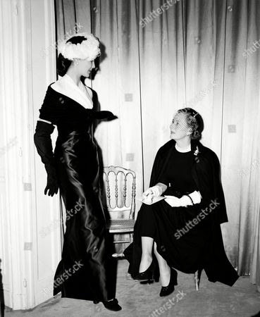 Dunne American actress Irene Dunne looks at a slim-lined Christian Dior evening gown, worn by a model, during her visit in Paris, France, on