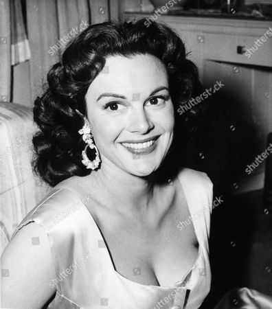 """Patricia Medina Patricia Medina, film star to appear in the """"What's My Line"""" TV game show, smiles in her room at London's Savoy Hotel, . She is wearing an ice-blue satin gown by Dior and large hoop pearl earrings"""
