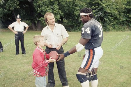 Walter Payton, Phil Collins, Simon Collins Pop Singer Phil Collins gets an autograph from Chicago Bears running back Walter Payton with his son, Simon, during a Bears workout in London on . The Bears are preparing for American Bowl ?86 game with the Dallas Cowboys