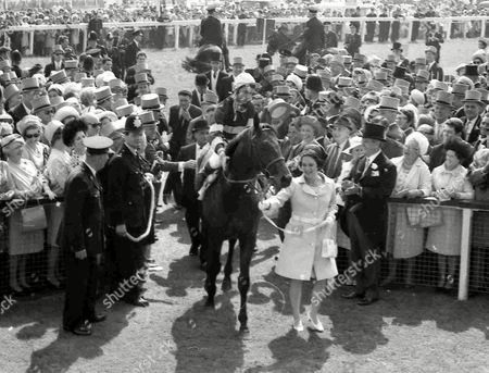 British jockey Lester Piggott riding 'Sir Ivor', is led into the winner's enclosure by Mrs Elizabeth Guest, at Epsom, England, after he had won the Derby