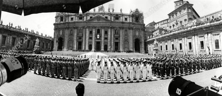 "Wide angle view of St. Peter's Square shortly after noon as honor units of the Italian armed forces are lined up while the newly elected Pope paul VI, formerly Giovanni Battista Cardinal Montini, Archbishop of Milan, gives his first blessing ""Urbi et Orbi"" (to Rome and to the World) from the central balcony of St. Peter's, background. What look as mouths of pieces of artillery in foreground are simply the mouths of some of the many long lens cameras pointed at the Basilica"