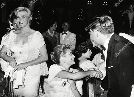 Stock Image of Princess Grace shakes hands with French singer Charles Trenet (partially hidden) at the Red Cross Gala in Monaco, . American Singer Rosemary Clooney stands smiling at left