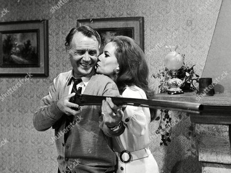 British Actor John Mills receives a kiss from Italian actress Luciana Paluzzi, during a break in the shooting of the movie 'Death has no sex', in a studio, in Rome, on
