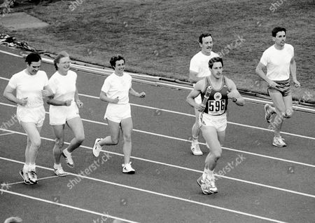 Scottish athlete Allan Wells holds the baton which contains the message from Britain's Queen Elizabeth II, whilst running around the track at the Meadowbank Stadium, Edinburgh, on