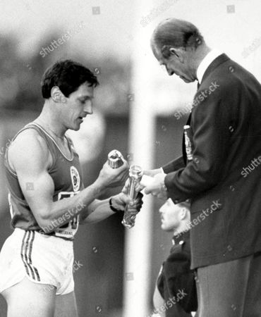 Scotland's Allan Wells, left, holds the baton from which the Duke of Edinburgh has removed the message from Britain's Queen Elizabeth II, which he will read to open the 13th Commonwealth Games at Meadowbank Stadium, Edinburgh, on