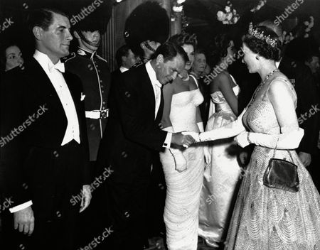 """American singer and actor Frank Sinatra is presented to Queen Elizabeth II in the foyer of the Odeon Theatre, Leicester Square, London, at the premiere of Danny Kaye's film, """"Me And The Colonel"""". Beyond him (partially obscured) is French actress Nicole Maurey"""