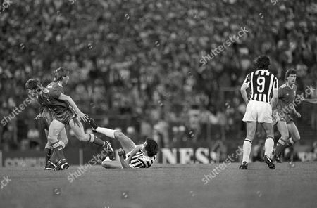 Jim Beglin, left, and Kenny Dalglish, right, from the FC Liverpool are pictured on the pitch after the first ten minutes of the European Champions final, in Brussels as Juventus Turin player Michael Platini is on the ground. The match has started after a nearly two-hour delay as uproar in the stadium prior to the game caused more than 30 deaths and hundreds of injuries