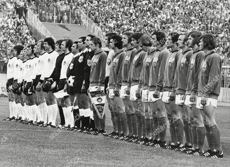 The teams from West Germany, in white shirts, and East Germany line up for the national anthems before the start of the Football World Cup Group 1 match at the Volksparkstadion, in Hamburg, on . The match ended in a 1 - 0 win for East Germany. From left to right West German team; Uli Hoeness, Paul Breitner, Berti Vogts, Jurgen Grabowski, Wolfgang Overath, Gerd Muller, Heinz Flohe, Hans-Georg Schwrzenbeck, Berhard Cullmann, goalkeeper Sepp Maier and captain Franz Beckenbauer. Referee Ramon Barreto of Uruguay stands between his two linesmen. East German team from left to right; Captain Bernd Bransch, goalkeeper Jurgen Croy, Jurgen Sparwasser, Hans-Jurgen Kreische, Harald Irmscher, Gerd Kische, Lothar Kurbjuweit, Reinard Lauck, Siegmar Watzlich, Konrad Weise and Martin Hoffmann