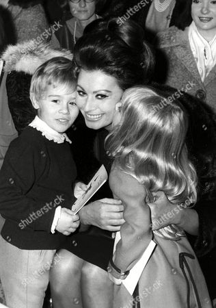 Stock Photo of Loren /1 - Gruppe Undated image taken in the early 1960s as Italian actress Sofia Loren (maiden name Sofia Scicolone) shares a tender moment hugging two models of a childrens' fashion show as a girl kisses Mrs. Loren on the cheek