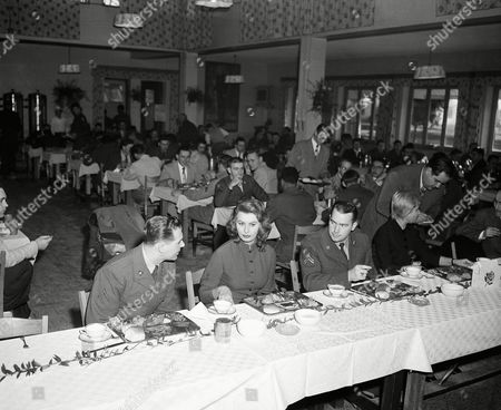 Italian movie actress Sophia Loren at Camp Darby, Leghorn, Italy on . General view of the mess hall during the lunch; in foreground, Sophia Loren between Pfc. Thomas, N.Y. (left) and Cpl. Donald Forrest, St. Louis, Mo